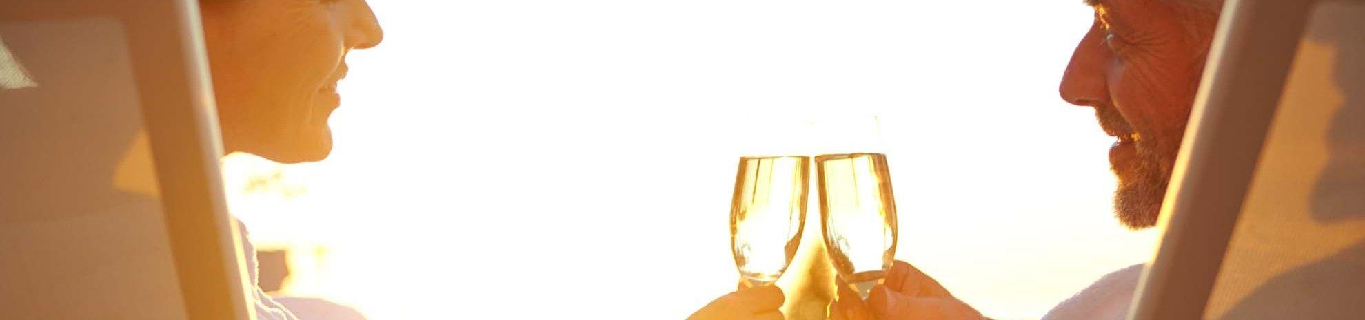 Couple qui trinque avec du champagne dans des transats