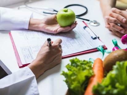 Main d'une personne réalisant une consultation diététique
