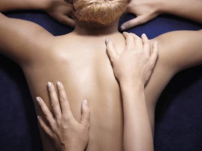 femme se faisant masser le dos durant un soin décontractant et reminéralisant avec les produits phytomer